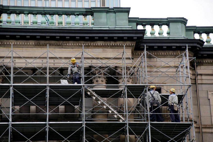 Workers are seen on scaffolds on the Bank of Japan building, which is undergoing construction works, in Tokyo.