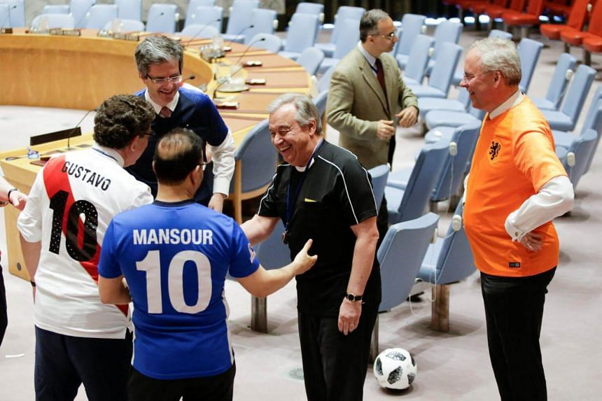 Members of the UN Security Council shake hands with Secretary General Antonio Guterres (in black). They are sporting jerseys to mark the opening match of the 2018 Fifa World Cup.