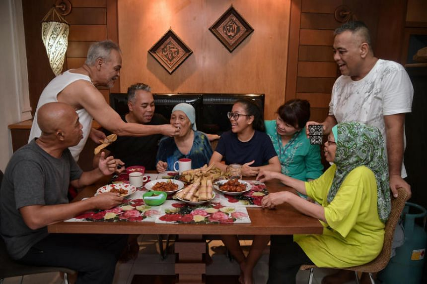 Mohd Noor Hashid (second from left) feeds his mother Madam Hajjah Marseah Bonoh as the rest of the family (from left) Omar Hashid, Ismail Hashid, Qurratu'aini Choi, Nur Qaisarah Alya Choi, Marianah Hashid (seated) and Zulkefli Hashid (standing) tak