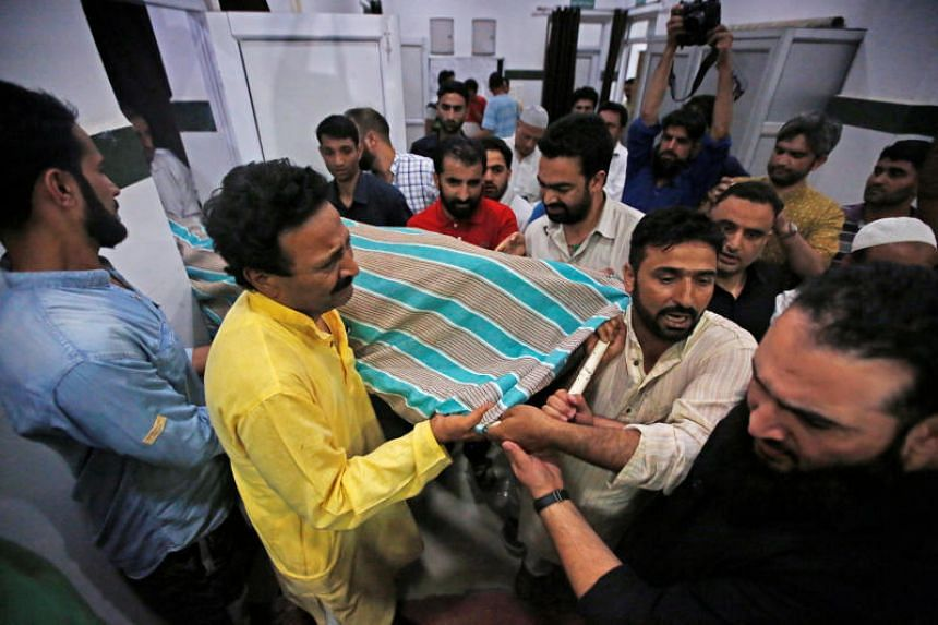 People carry the body of Syed Shujaat Bukhari, the editor of Rising Kashmir daily newspaper, who was killed by unidentified gunmen outside his office in Srinagar, on June 14, 2018.