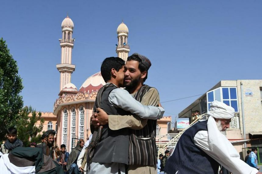 Afghan residents greet each other after al-Fitr prayers marking the end of the holy month of Ramadan, in Ghani on June 15, 2018.