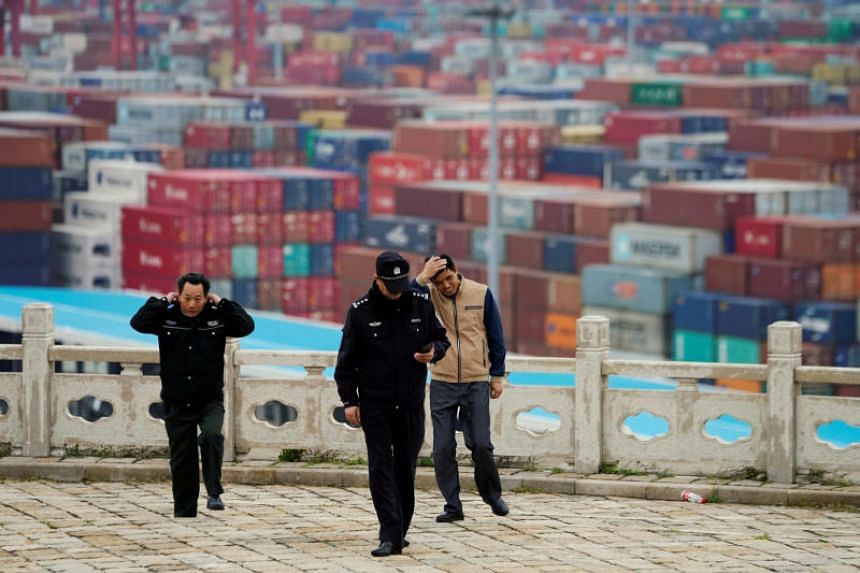 Security guards walk in front of containers at the Yangshan Deep Water Port in Shanghai, China, on April 24, 2018.