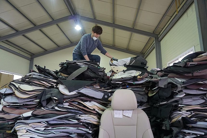 A worker sorting recovered car leather in Morethan's warehouse. Company founder Ian Choi (below) is surrounded by products made using leather from old car seats.