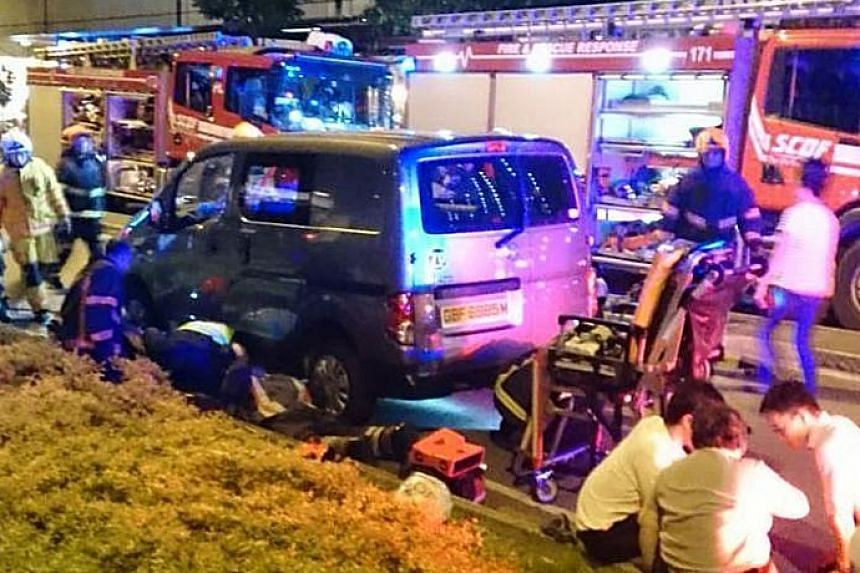A woman trapped under a van was freed using hydraulic rescue tools and taken to hospital.