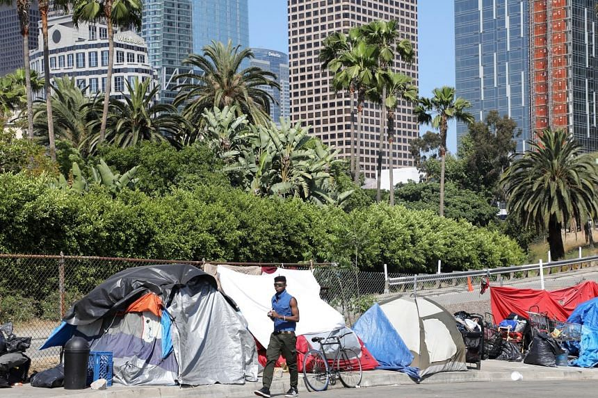 The tents of homeless people (above) lining a street leading into the burgeoning downtown skyline of Los Angeles, California. (Below) A homeless man in Worcester, Massachusetts.