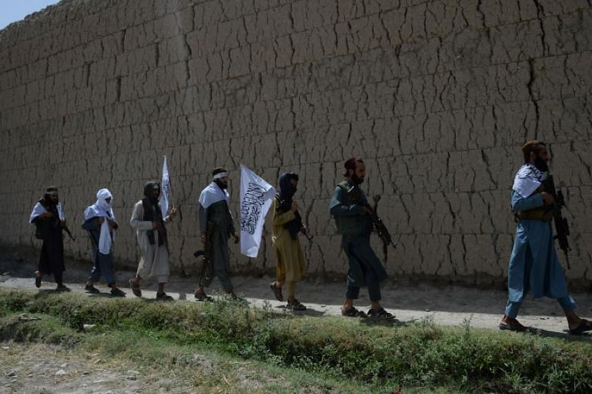 Afghan Taliban militants walk as they took to the street to celebrate ceasefire on the second day of Eid in the outskirts of Jalalabad on June 16, 2018.