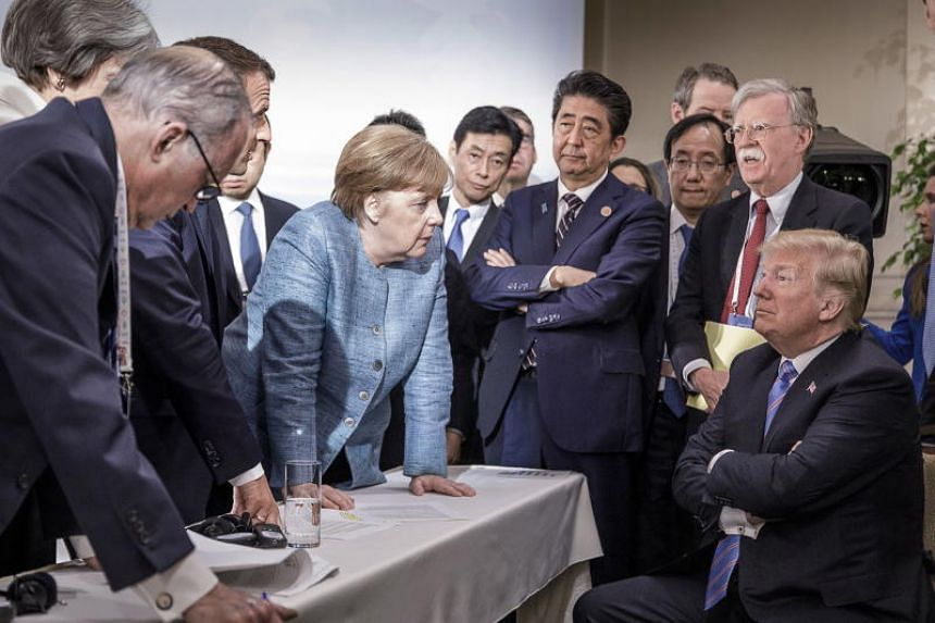 French President Emmanuel Macron, German Chancellor Angela Merkel and Japan's Prime Minister Shinzo Abe speaking to US President Donald Trump during the second day of the G7 meeting in Charlevoix, on June 9, 2018.