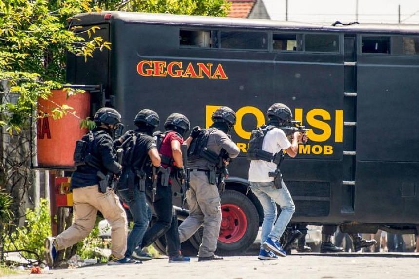 Members of Indonesia's Densus 88 counter-terror police squad conduct a raid on the residence where a family suspected of taking part in recent suicide bombings resided in, in Surabaya, on May 15, 2018.