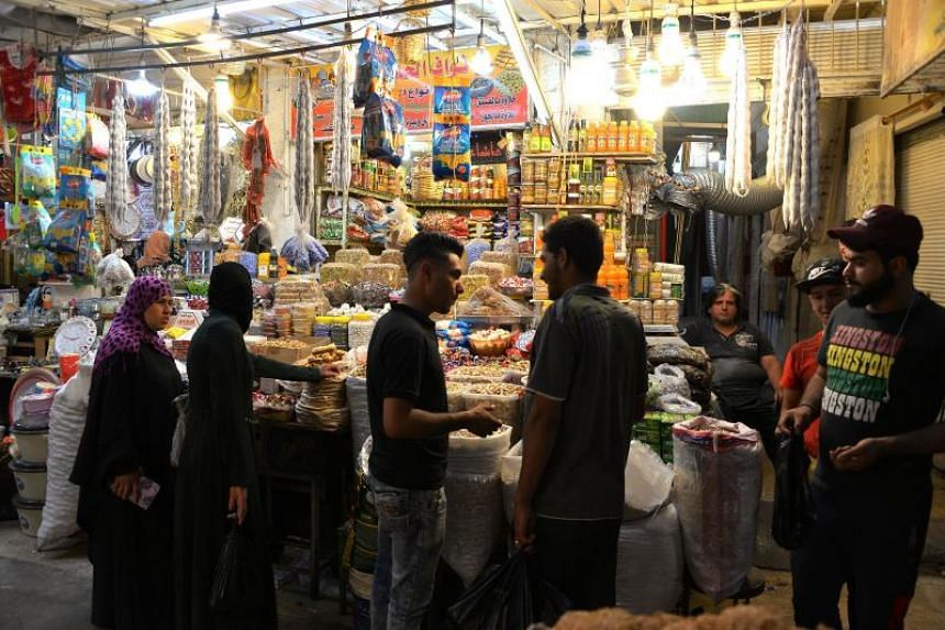 Iraqis shop for nuts, sweets, and dried fruits at a market on the last day of the Muslim holy month of Ramadan before celebrating the first day of the Eid al-Fitr holiday the next day in the northern city of Mosul on June 14, 2018.