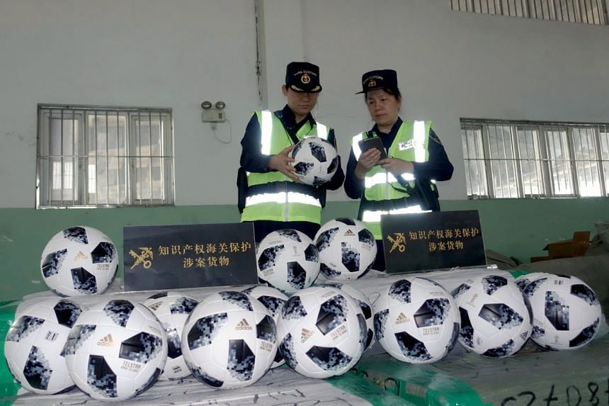 Customs officials inspecting suspected counterfeit World Cup goods in Guangzhou.