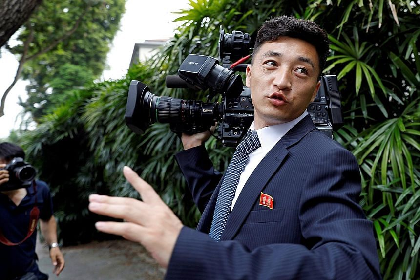 A North Korean cameraman outside The St Regis Singapore hotel, where leader Kim Jong Un stayed. The country's camera crew had earned themselves a reputation for photobombing at the inter-Korea summit in April. A North Korean security agent guarding t
