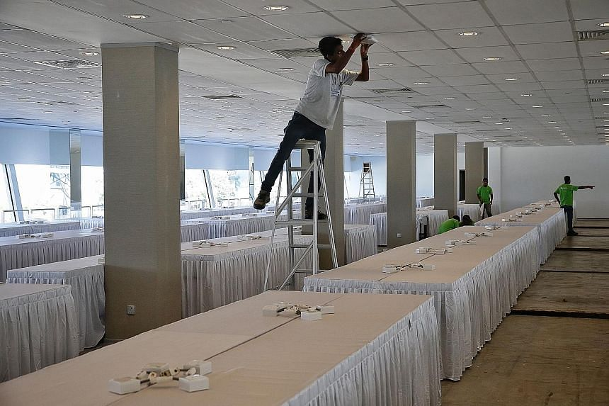 Workers setting up rooms at the F1 Pit Building, which was converted into a media centre for over 2,500 journalists who covered the summit. Mr Kim's decision to visit Marina Bay Sands, Gardens by the Bay and Jubilee Bridge (above) on Monday night was