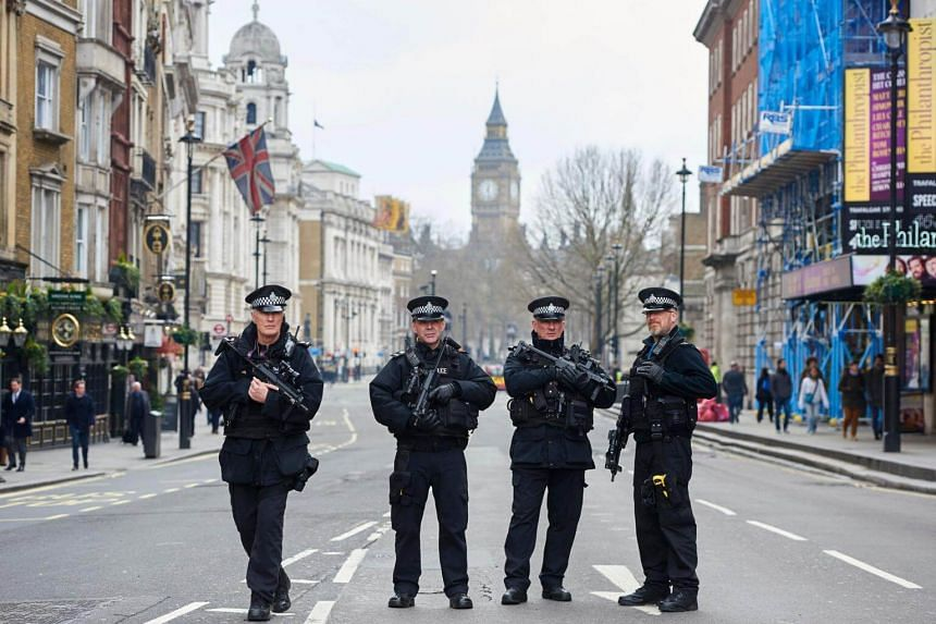 Armed police officers secure the area on Whitehall leading towards the Houses of Parliament in central London, on March 23, 2017.