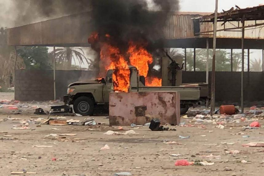 An armoured vehicle on fire as Yemeni pro-government forces conduct an attack on Huthi rebels positions in the area of al-Fazah in Yemen's Hodeida province, on June 16, 2018.