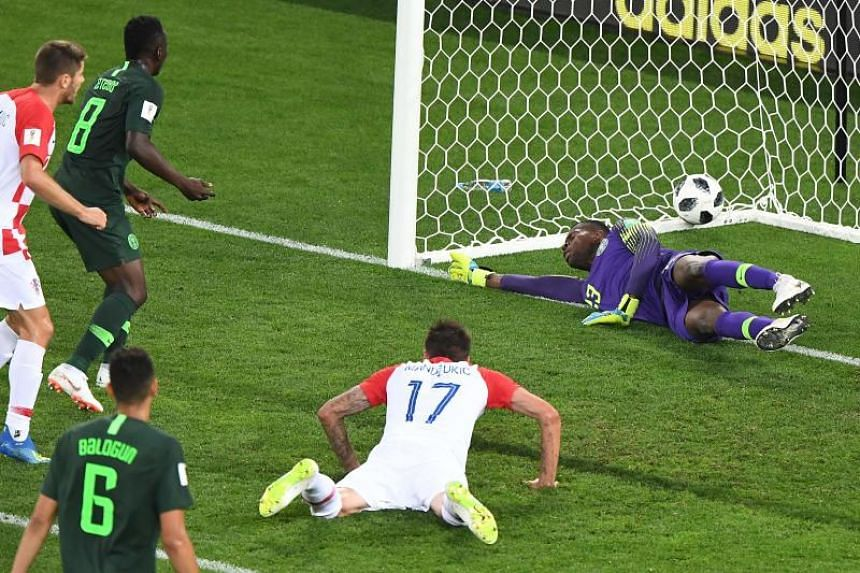 Croatia's forward Mario Mandzukic (right) dives and Nigeria's midfielder Oghenekaro Etebo (second from left) scores an own goal against teammate Nigeria's goalkeeper Francis Uzoho at the Kaliningrad Stadium in Kaliningrad on June 16, 2018.