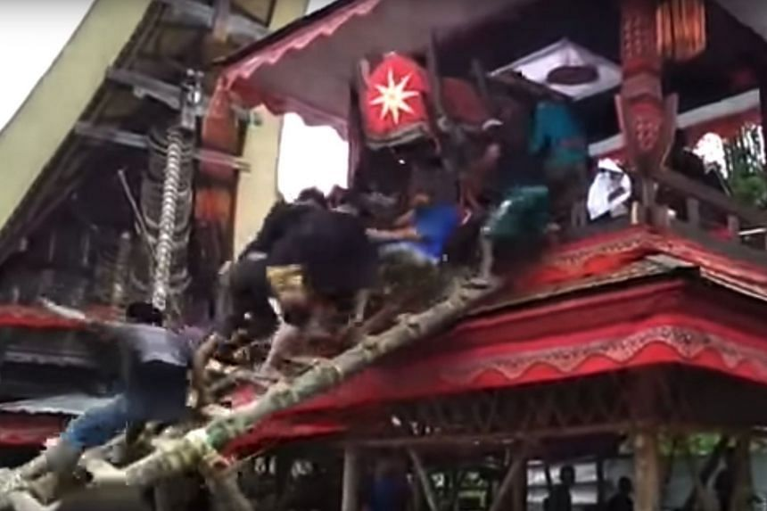 A crowd climbing a bamboo ladder to put the coffin inside a traditional wooden stilt house, before the ladder suddenly broke and the carriers lost control of the coffin.