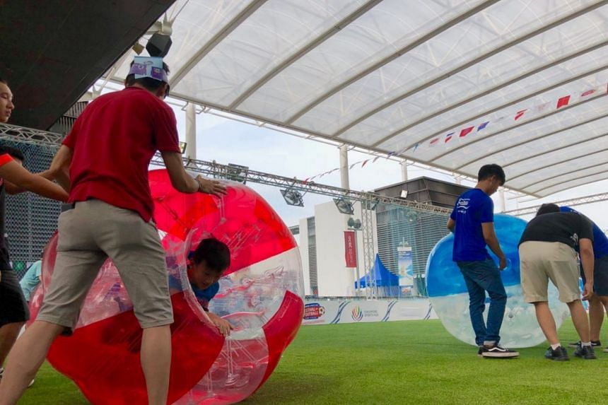 Fathers and children bonding by rolling each other in giant inflatable balls at Dad's Day Out at the Singapore Sports Hub on June 17 to celebrate Father's Day.