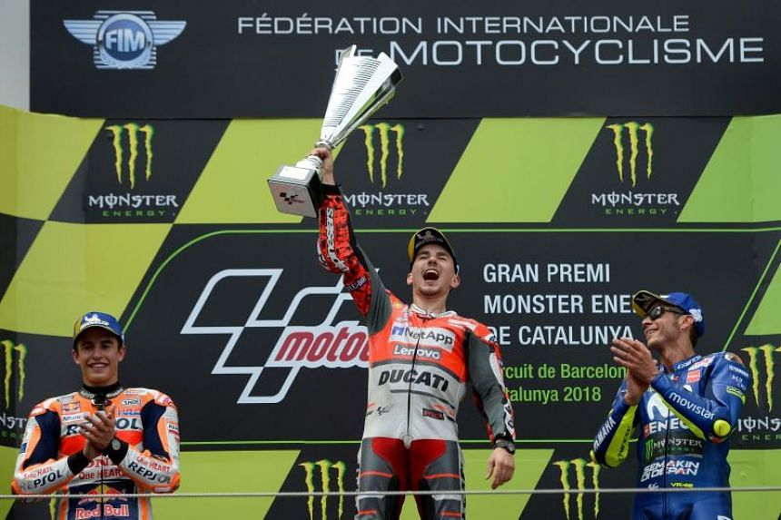 Ducati's Jorge Lorenzo (centre) celebrating on the podium, together with Honda's Marc Marquez (left) and Yamaha's Valentino Rossi, after winning the Catalunya MotoGP Grand Prix on June 17, 2018.