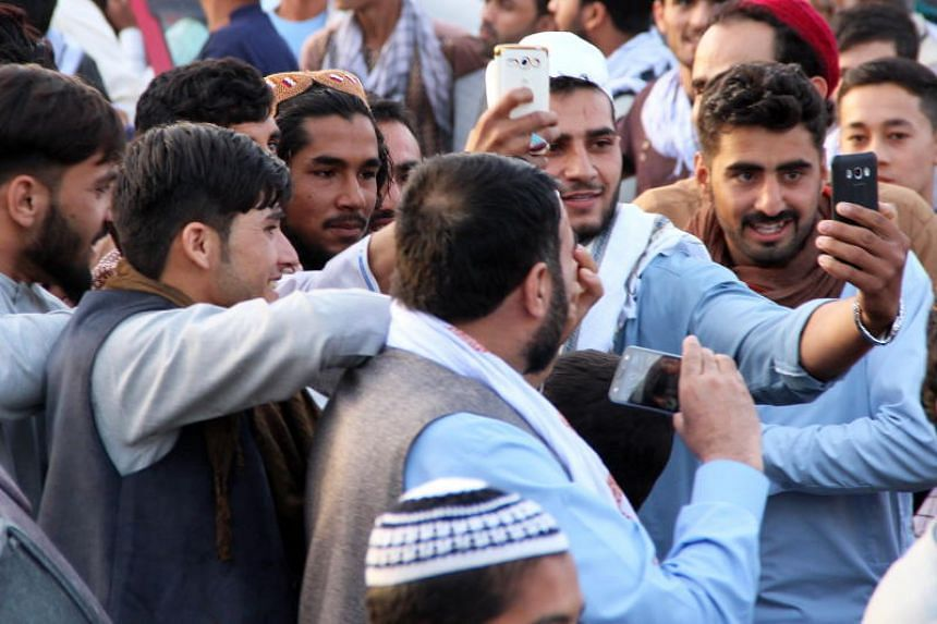 People taking selfies with an alleged Taleban militant after a group of them visited a bazaar as a goodwill gesture during a ceasefire, in Kunduz, Afghanistan, on June 15, 2018.