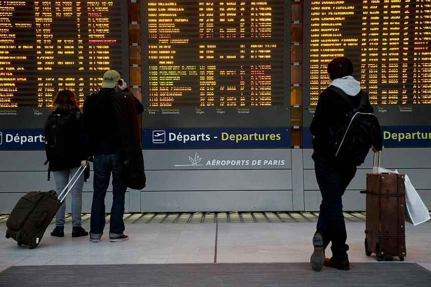 Passengers reading a departure board during a nationwide strike to protest against job cuts, at Roissy Charles-de-Gaulle airport in France, on Jan 26, 2016.