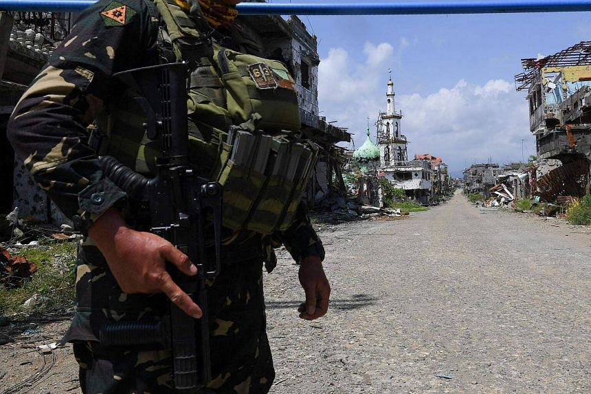 File photo showing a soldier standing guard next in a road leading to a destroyed mosque in Marawi City, on southern island of Mindanao, on April 1, 2018.