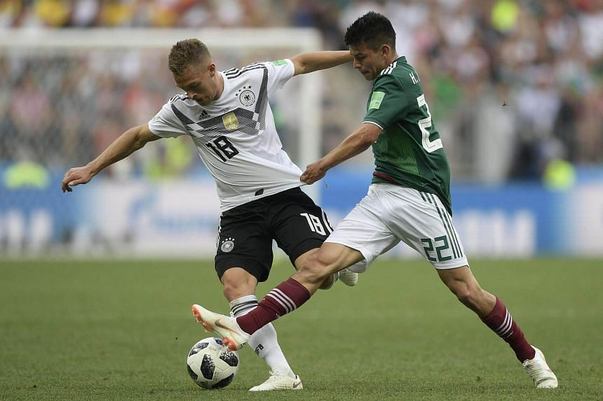 Germany's defender Joshua Kimmich (left) and Mexico's forward Hirving Lozano compete for the ball during the Russia 2018 World Cup Group F football match between Germany and Mexico at the Luzhniki Stadium in Moscow, Russia, on June 17, 2018.