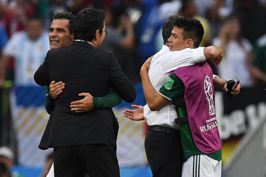Mexico's midfielder Rafael Marquez (left) and and Mexico's forward Hirving Lozano (right) celebrate with Mexico's coach Juan Carlos Osorio (second right) at the end of the match against Germany at the Luzhniki Stadium in Moscow, Russia, on June 17, 2