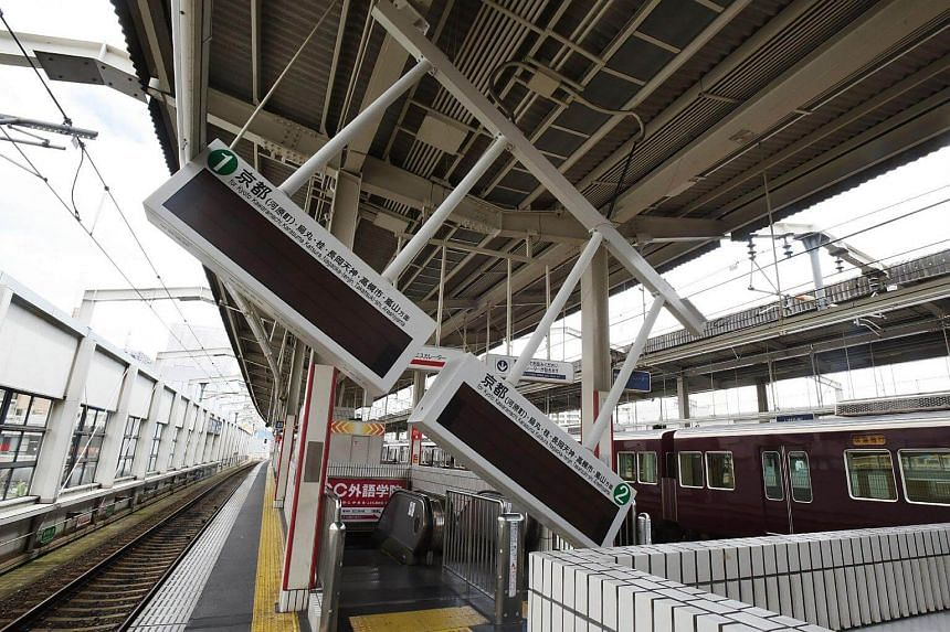 Train guide electric boards tilt following an earthquake at Ibaraki-shi Station in Ibaraki City, north of Osaka, on June 18, 2018.
