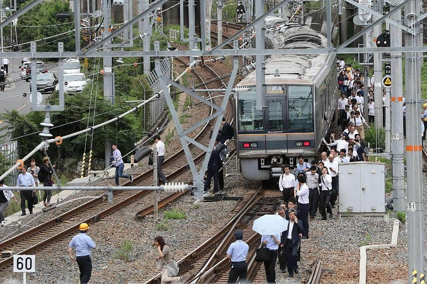 Passengers from a train walk along railroad tracks following an earthquake in Osaka, on June 18, 2018.
