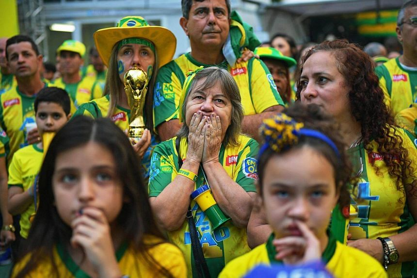 Fans of Brazil react after Switzerland equalised, during a broadcast of the World Cup 2018 football match on a big outdoor screen in the Alzirao neighborhood, in Rio de Janeiro, on June 17, 2018.