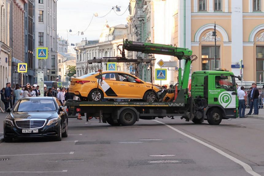 A damaged taxi, which ran into a crowd of people, is evacuated in central Moscow, Russia, on June 16, 2018.