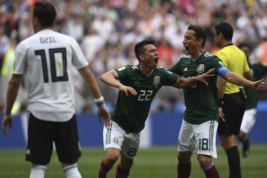 Mexico's forward Hirving Lozano (centre) celebrates with Mexico's midfielder Andres Guardado (right) after scoring a goal during the Russia 2018 World Cup Group F football match between Germany and Mexico at the Luzhniki Stadium in Moscow on June 17,