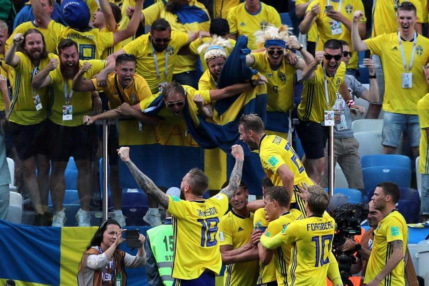 Sweden's players celebrate their first goal with fans during their World Cup Group F match against South Korea on June 18, 2018.
