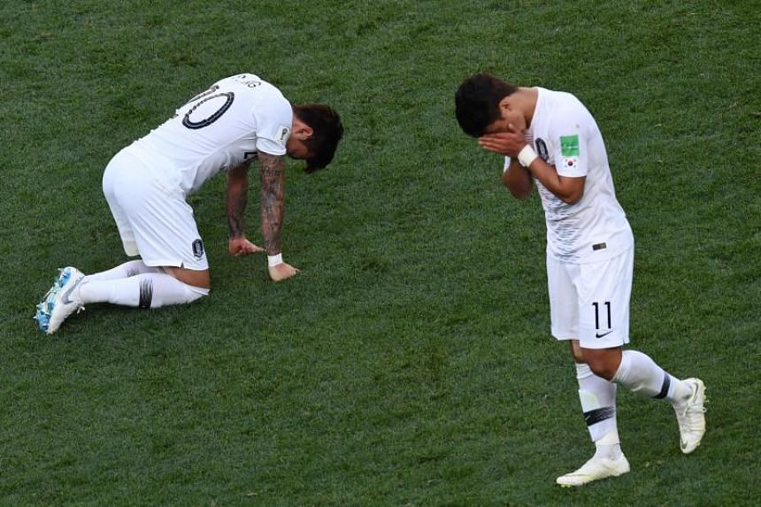 South Korea's Hwang Hee Chan (right) and Jang Hyun Soo react to their loss during their World Cup Group F match against Sweden on June 18, 2018.