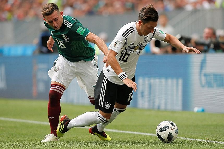 Mexico's Hector Herrera (left) kept a close eye on Germany's Mesut Ozil on Sunday. The Mexicans upset the defending champions 1-0.