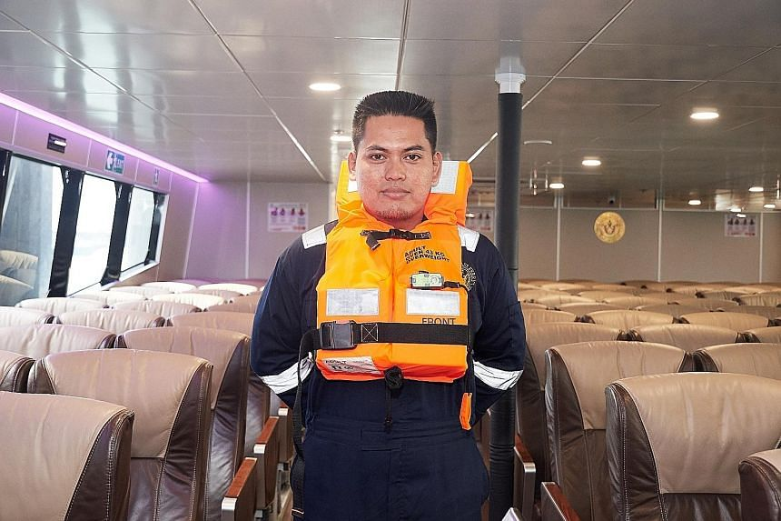 Majestic Dream ferry chief engineer Abdurrahman Basuni, 35, wearing an older string-type life jacket and the new buckle-type life jacket (above), which is in use on his vessel.