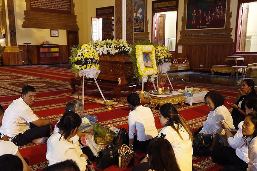Above: Mourners sitting near a coffin containing the remains of Prince Norodom Ranariddh's wife Ouk Phalla, at a pagoda in Phnom Penh yesterday. Left: Prince Ranariddh and his wife attending a congress in Phnom Penh in January 2015.