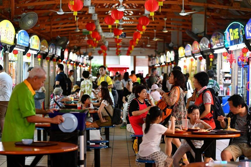"""File photo showing a hawker centre in Singapore. Currently, food establishments are graded A, B, C or D annually based on a """"snapshot assessment"""" of their premises."""
