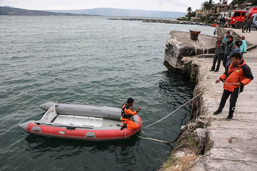 Indonesian rescuers prepare their boat before they start a search and rescue operation for a sunken boat at Lake Toba, in North Sumarta, Indonesia, on June 19, 2018.