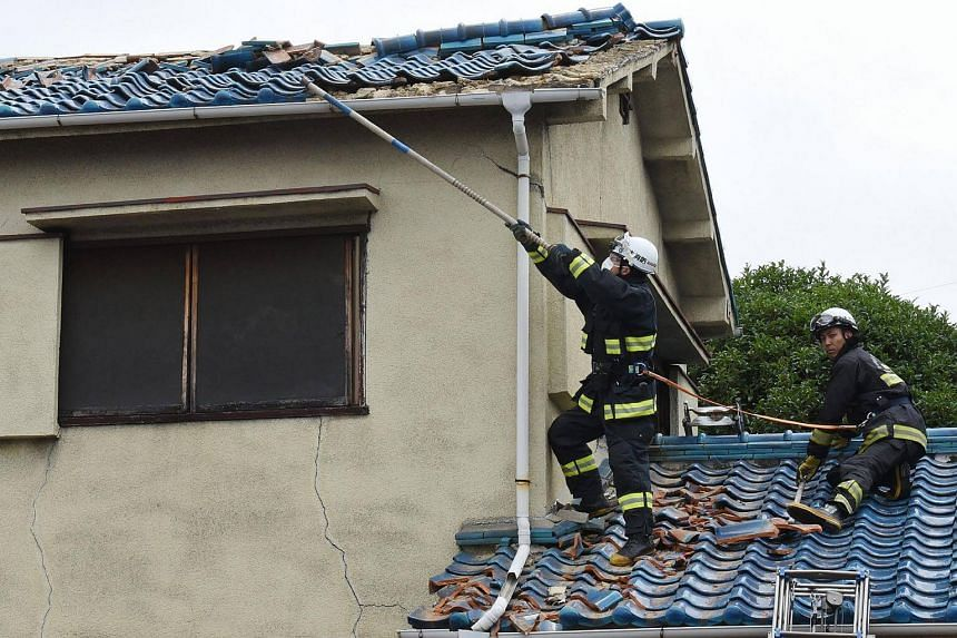 Firefighters checking a house damaged by an earthquake in Ibaraki City, north of Osaka prefecture, on June 18, 2018.