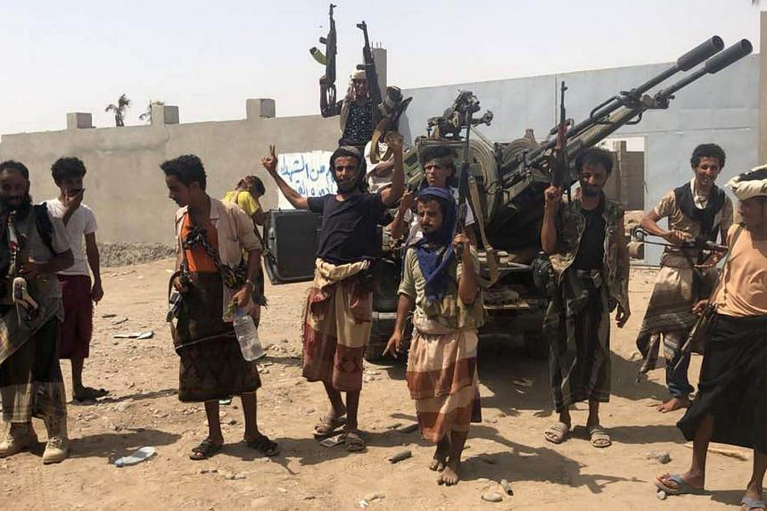 Yemeni pro-government forces backed by the Saudi-led Arab military alliance gather during their fight against Huthi rebels in the area of Hodeida's airport, on June 18, 2018.