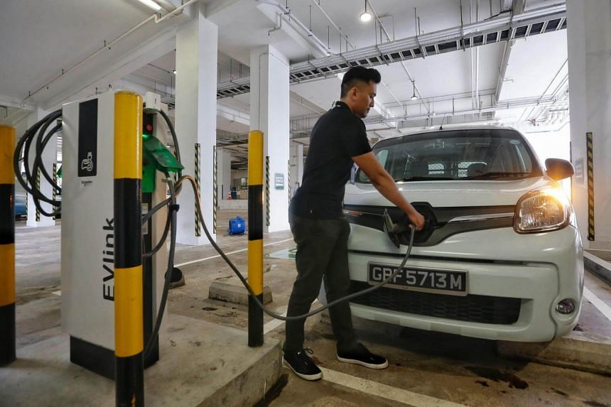 SP Group technical officer Muhammad Ismadi Kamsani, 29, charging an electric vehicle from a charging point, on June 19, 2018.
