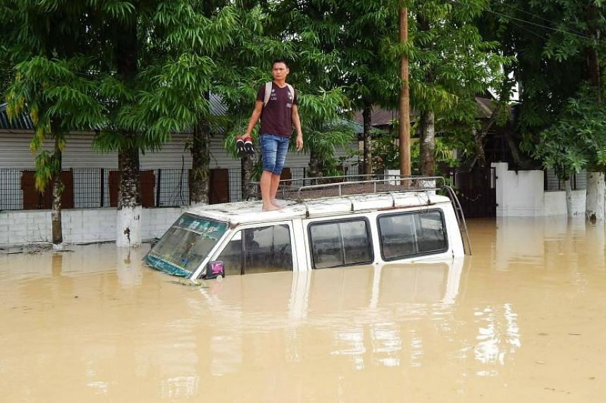 An Indian resident stands on the roof of a partially submerged car after a heavy downpour at Kailasahar on June 14, 2018.