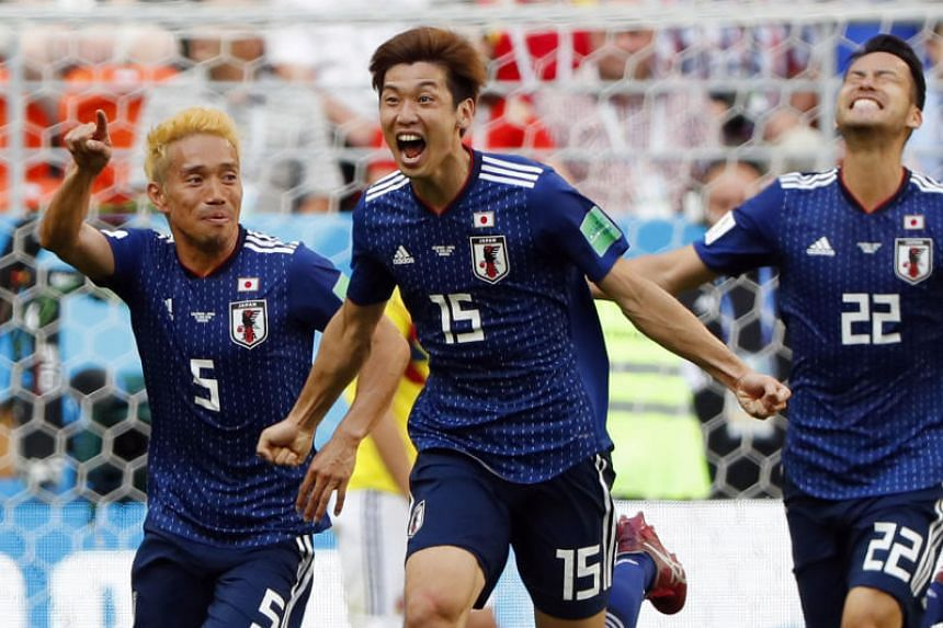 Japan's Yuya Osako (centre) celebrating with teammates Yuto Nagatomo (left) and Maya Yoshida after scoring against Colombia during their World Cup match on June 19, 2018.
