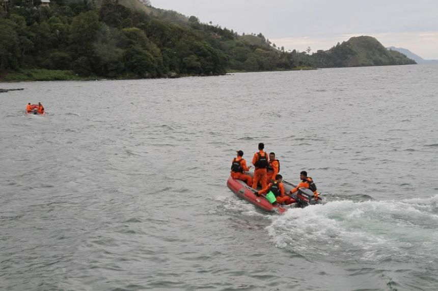 Rescue teams continue to search for victims at the Lake Toba ferry port in North Sumatra on June 19, 2018.