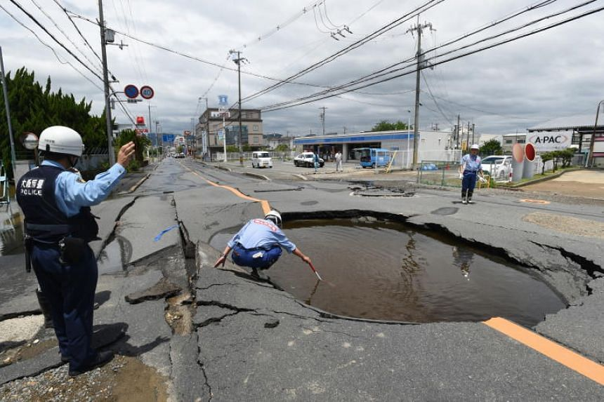 Workers check damage on a road collapsed by an earthquake in Takatsuki, Osaka Prefecture in Japan, on June 18, 2018.