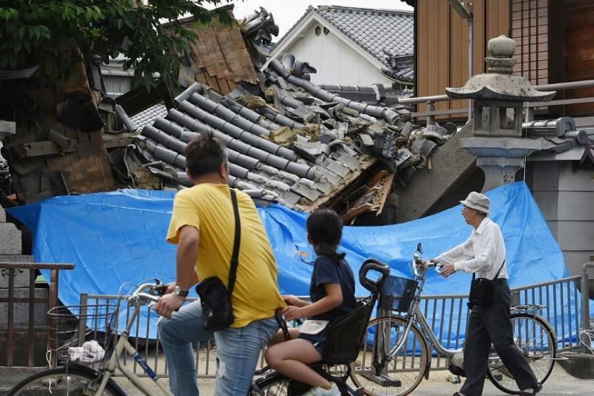 People pause to look at a collapsed house following an earthquake in Ibaraki City, north of Osaka prefecture, on June 18, 2018.