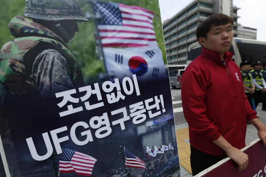 A South Korean holds a placard during a protest near the US embassy in Seoul, South Korea, on June 15, 2018. The Ulchi Freedom Guardian exercises is an annual joint war exercise between the South Korean and US military forces.