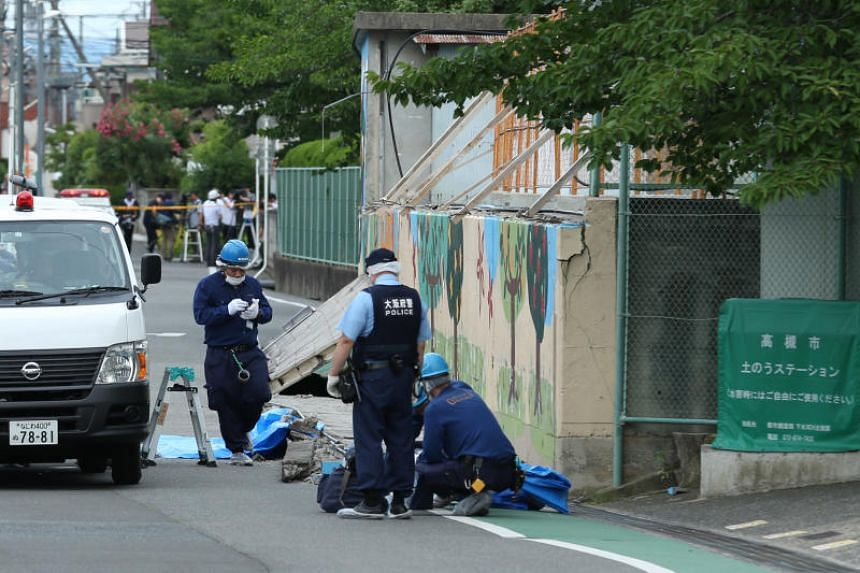 Police officers investigate the site where an elementary school student was killed after the walls next to the school pool had collapsed due to a magnitude 6.1 earthquake in Takatsuki, Osaka, Japan, on June 18, 2018.