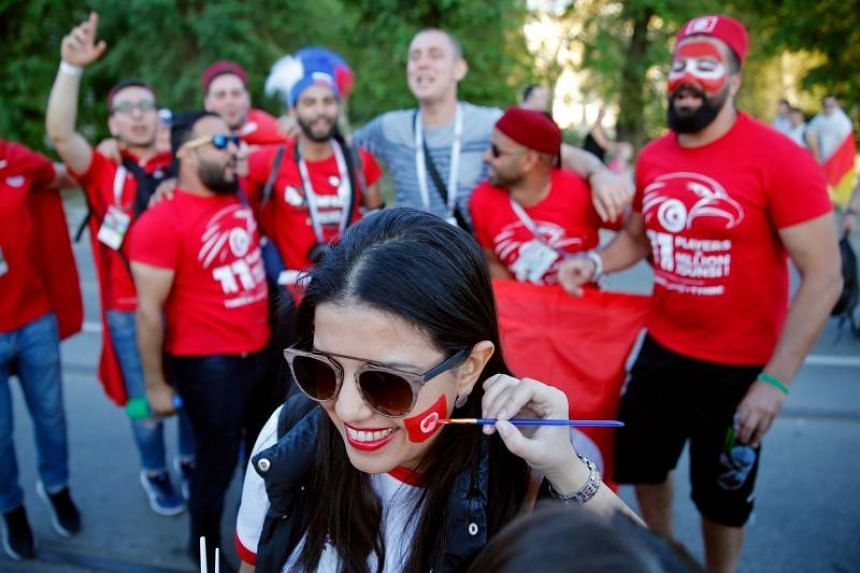 A girl paints the face of a Tunisian fan with her national flag on their way to the Russia 2018 World Cup Group G football match between Tunisia and England at the Volgograd Arena in Volgograd on June 18, 2018.